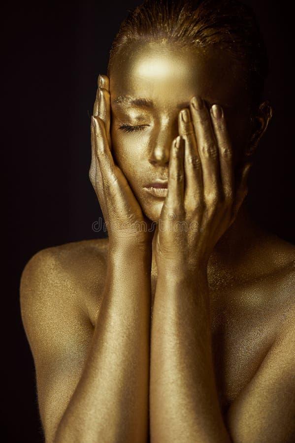 Απόκοσμα χρυσά κορίτσια πορτρέτου, χέρια κοντά στο πρόσωπο Πολύ λεπτός και θηλυκός Τα μάτια είναι κλειστά στοκ φωτογραφία με δικαίωμα ελεύθερης χρήσης