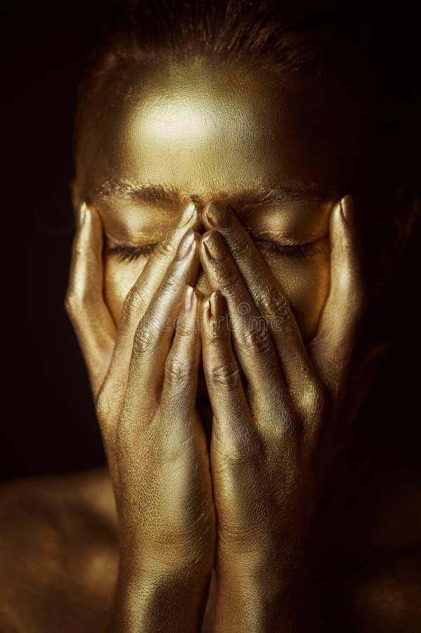 Απόκοσμα χρυσά κορίτσια πορτρέτου, χέρια κοντά στο πρόσωπο Πολύ λεπτός και θηλυκός Τα μάτια είναι κλειστά στοκ εικόνα