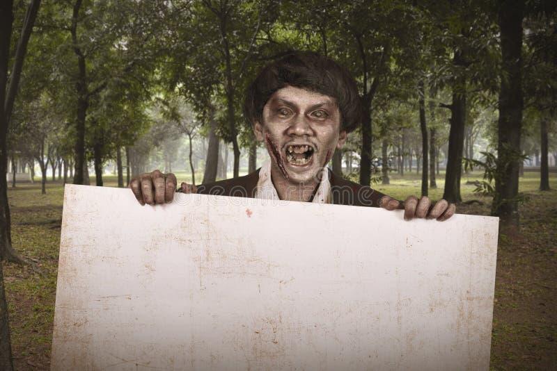 Απόκοσμο ασιατικό άτομο zombie στο κοστούμι με το κενό έμβλημα στοκ φωτογραφία με δικαίωμα ελεύθερης χρήσης