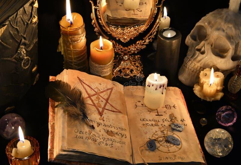 Απόκρυφο υπόβαθρο με το μαύρο μαγικό βιβλίο, καίγοντας κεριά και mirrow στοκ φωτογραφία
