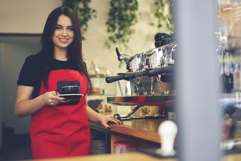 Απόλαυση σερβιτορών χαμόγελου ελκυστική θηλυκή που λειτουργεί το φλυτζάνι cappuccino εκμετάλλευσης διαδικασίας στοκ εικόνες