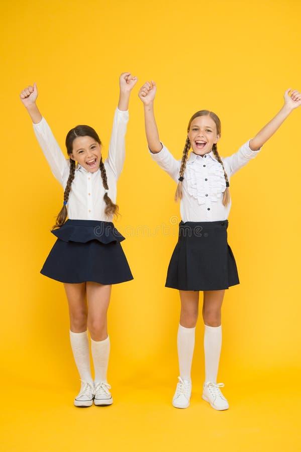 Απόλαυση της επιτυχίας Ευτυχή παιδιά που γιορτάζουν την επιτυχία στο κίτρινο υπόβαθρο Μικρές μαθήτριες που διεγείρονται περίπου στοκ φωτογραφία με δικαίωμα ελεύθερης χρήσης