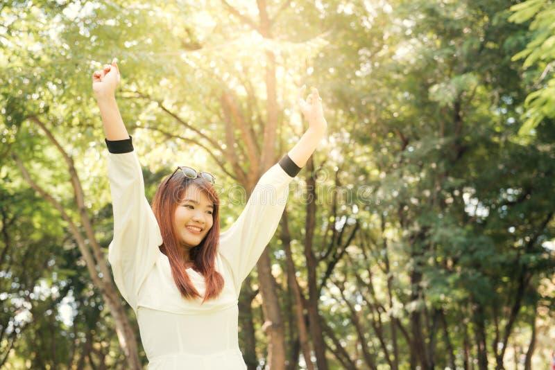 απόλαυση της φύσης Η νέα ασιατική γυναίκα οπλίζει αυξημένος απολαμβάνοντας το καθαρό αέρα στο πράσινο δάσος στοκ φωτογραφία με δικαίωμα ελεύθερης χρήσης