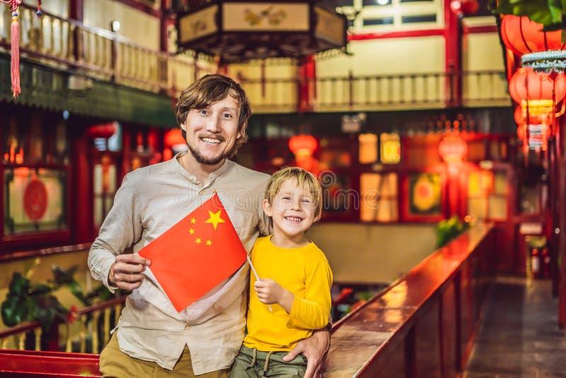 Απόλαυση των διακοπών στην Κίνα Ο ευτυχείς μπαμπάς και ο γιος τουριστών με έναν Κινέζο σημαιοστολίζουν σε ένα κινεζικό υπόβαθρο Τ στοκ εικόνες
