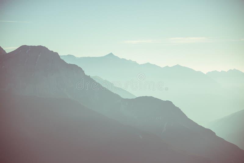 Απόμακρη σκιαγραφία βουνών με το σαφή ουρανό και το μαλακό φως Τονισμένη εικόνα, εκλεκτής ποιότητας φίλτρο, διασπασμένος τονισμός στοκ φωτογραφία