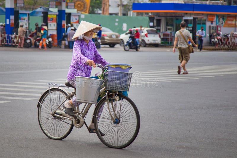 Απόμερη γυναίκα που οδηγά ένα bycicle στη πόλη Χο Τσι Μινχ στοκ εικόνα