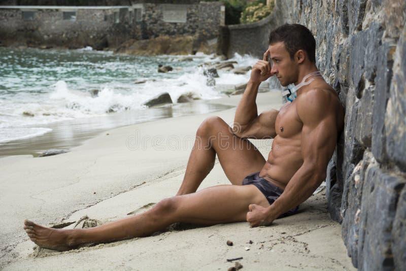 Απόμερος αθλητικός νεαρός άνδρας στην παραλία που ακούει τη μουσική στοκ εικόνα με δικαίωμα ελεύθερης χρήσης