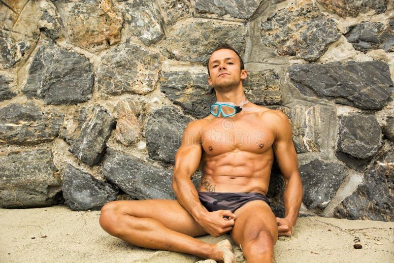 Απόμερος αθλητικός νεαρός άνδρας στην παραλία που ακούει τη μουσική στοκ φωτογραφία με δικαίωμα ελεύθερης χρήσης