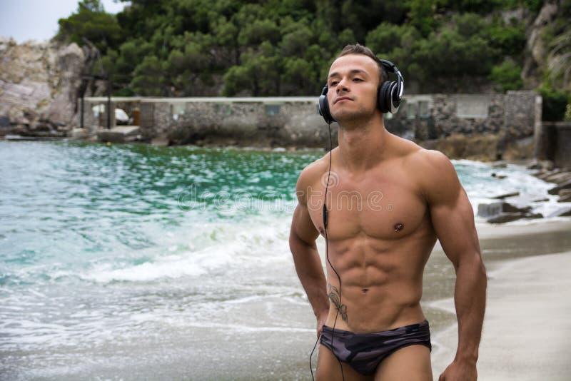 Απόμερος αθλητικός νεαρός άνδρας στην παραλία που ακούει τη μουσική στοκ εικόνα