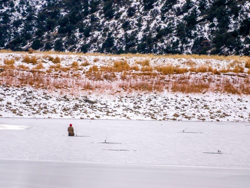 Απόμερος ψαράς πάγου που γονατίζει στον πάγο στοκ εικόνες