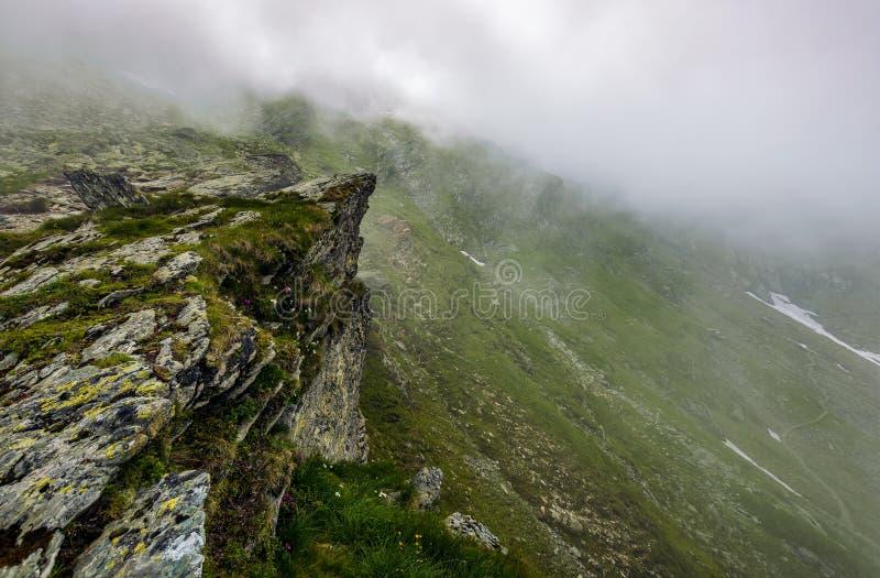 Απότομη κλίση στη δύσκολη βουνοπλαγιά στην ομίχλη στοκ φωτογραφίες