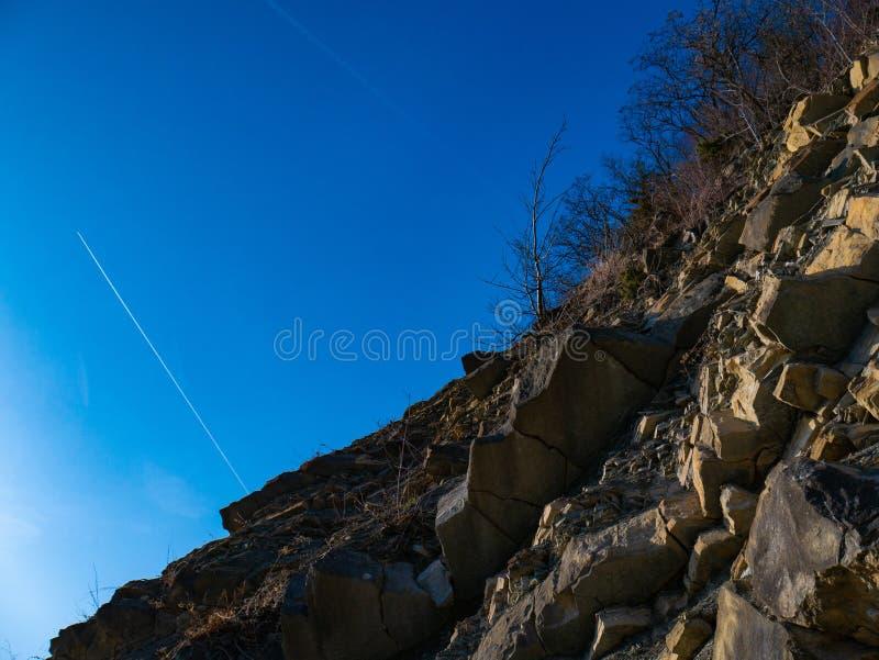 Απότομος βράχος και μπλε ουρανός και αεροπλάνο στοκ φωτογραφία με δικαίωμα ελεύθερης χρήσης