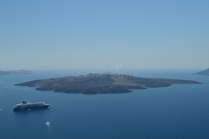 Απόψεις του κόλπου Thera από Fira με μια δεμένη κρουαζιέρα σε το και την όμορφη άποψη του νησιού που κάθεται απέναντι από Αρχιτεκ στοκ φωτογραφία