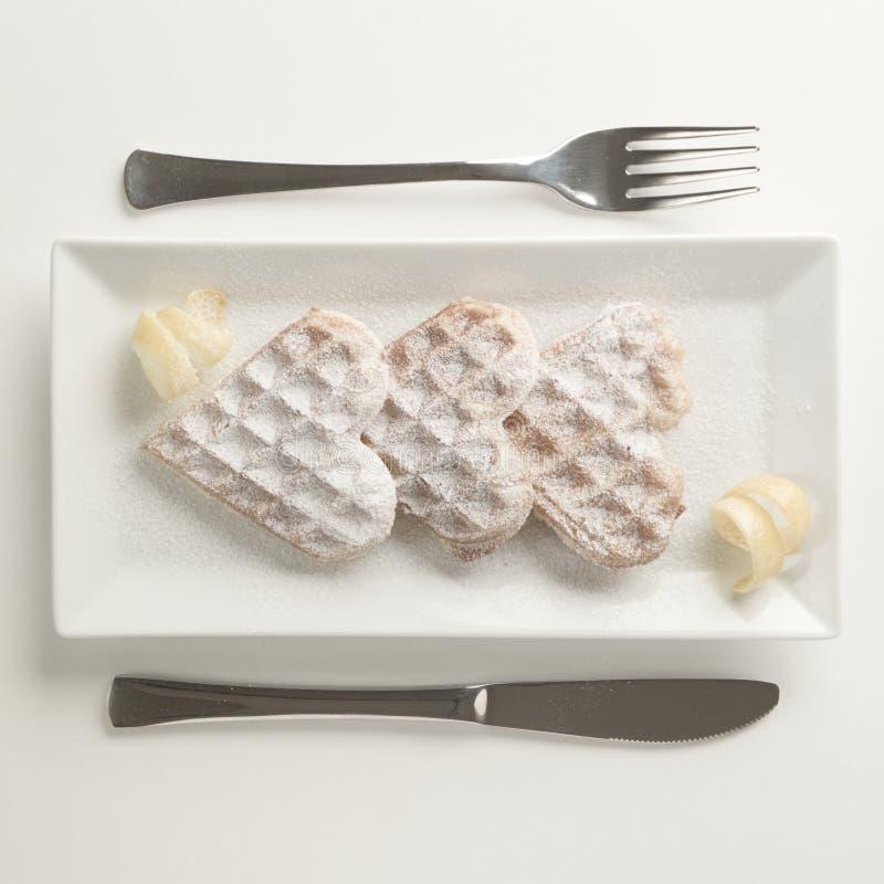Απόλαυση λεμονιών βαφλών καρδιών, κονιοποιημένη ζάχαρη που εξυπηρετείται στο ορθογώνιο π στοκ φωτογραφία με δικαίωμα ελεύθερης χρήσης