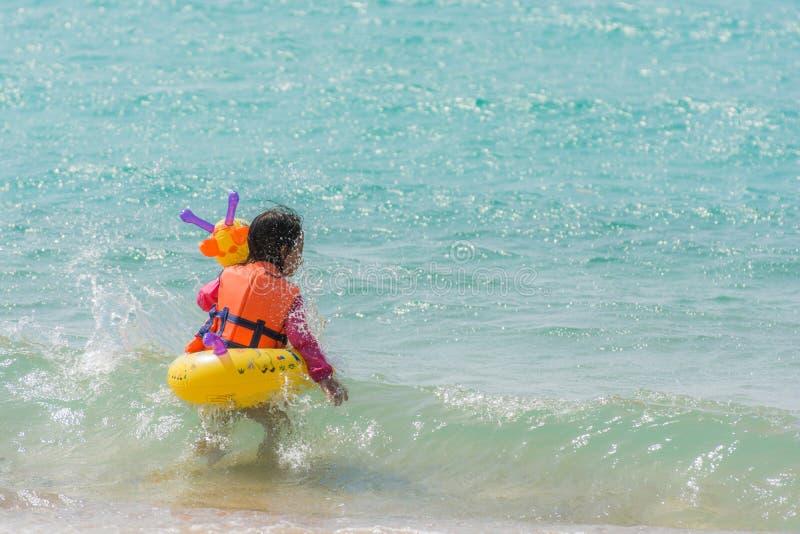 Απόλαυση κοριτσιών παιδιών που κολυμπά στη θάλασσα με λαστιχένιο giraffe δαχτυλιδιών στοκ εικόνα με δικαίωμα ελεύθερης χρήσης
