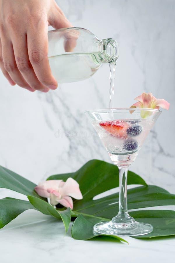 Από κοντά, ο μπάρμαν αναμιγνύει σόδα με φράουλες και βατόμουρα σε ένα ποτήρι για να ετοιμάσει ένα κοκτέιλ στα πράσινα φύλλα στοκ εικόνες με δικαίωμα ελεύθερης χρήσης
