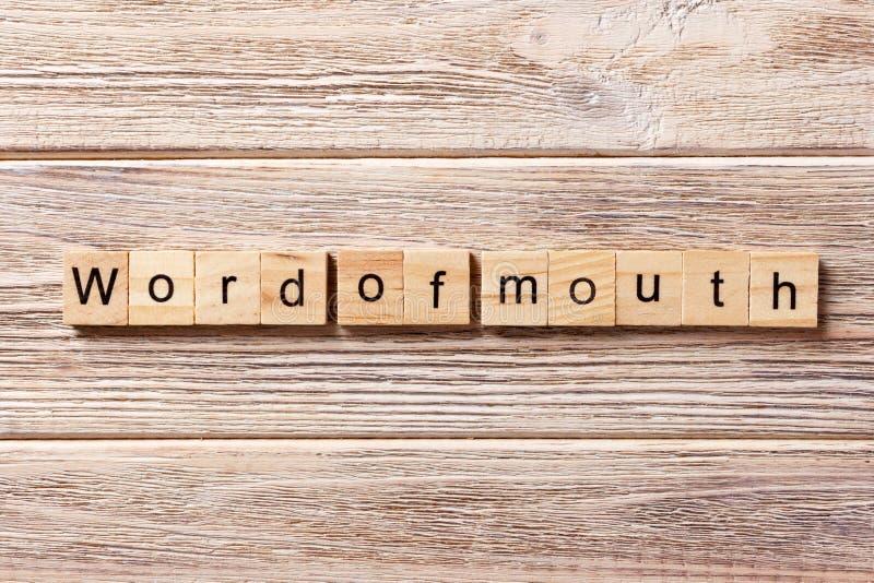 Από στόμα σε στόμα λέξη που γράφεται στον ξύλινο φραγμό Από στόμα σε στόμα κείμενο στον πίνακα, έννοια στοκ εικόνα