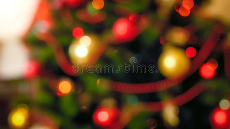 Από την εικόνα εστίασης των κόκκινων και χρυσών μπιχλιμπιδιών που κρεμούν στο χριστουγεννιάτικο δέντρο στο καθιστικό στοκ φωτογραφίες