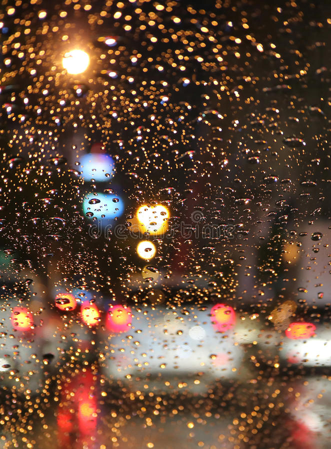 Από την εστίαση της κυκλοφοριακής συμφόρησης στη βροχερή νύχτα που βλέπει από τον ανεμοφράκτη αυτοκινήτων με τις σταγόνες βροχής στοκ φωτογραφίες