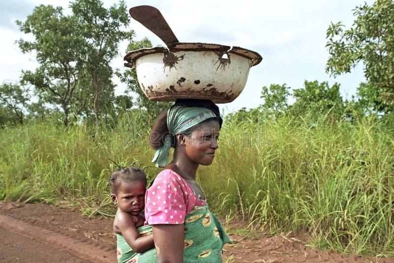Από τη Γκάνα γυναίκα lugging τα εργαλεία παιδιών και κουζινών στοκ φωτογραφίες με δικαίωμα ελεύθερης χρήσης