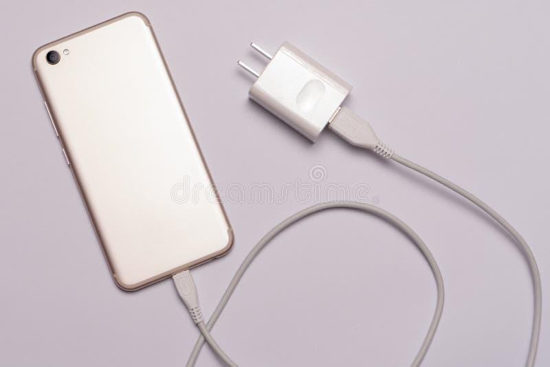 από το άσπρο έξυπνο τηλέφωνο, φορτιστής με το καλώδιο στοκ εικόνα με δικαίωμα ελεύθερης χρήσης