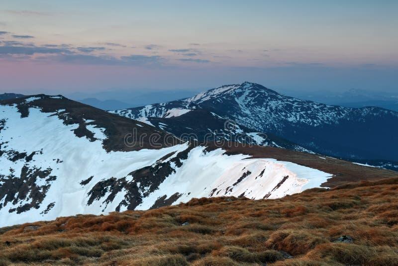 Από το λιβάδι ανοίγει μια πανοραμική άποψη των βουνών, που φωτίζεται από τις ακτίνες ήλιων πρωινού Ανατολή ουρανός σύννεφων στοκ φωτογραφίες