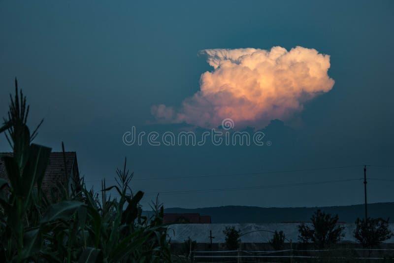Από το μουντό στρώμα μια καταιγίδα αυξάνεται επάνω και φωτίζεται υπέροχα από τον ήλιο ρύθμισης στοκ εικόνες