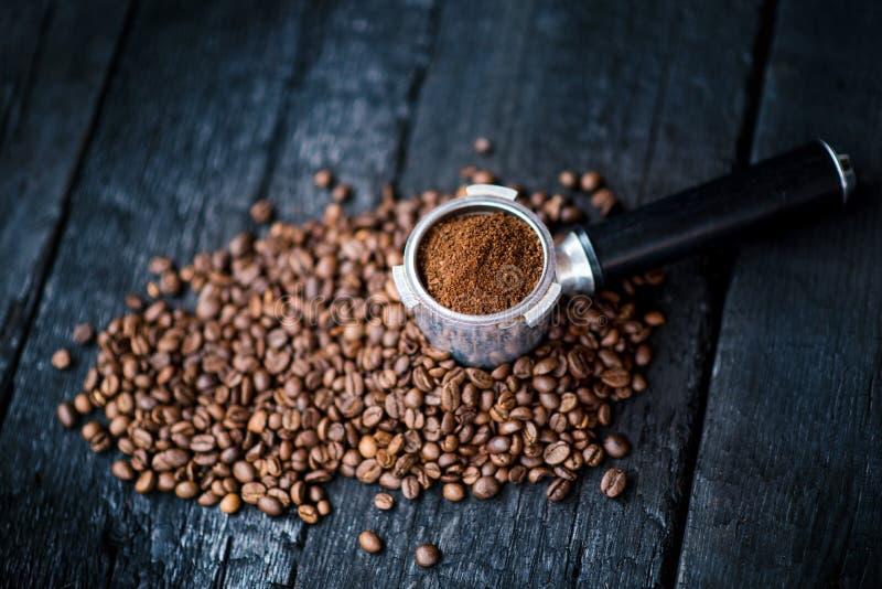Απύθμενο φίλτρο με τα φασόλια αλέσματος σε έναν ξύλινο μαύρο πίνακα καφές φασολιών που ψήνεται Εξαγωγή καφέ Espresso Προετοιμαστε στοκ εικόνες