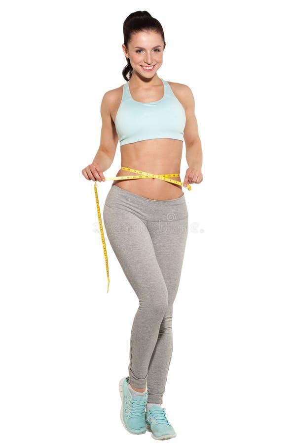 Απώλεια βάρους, αθλητικό κορίτσι που μετρά τη μέση της στοκ εικόνα