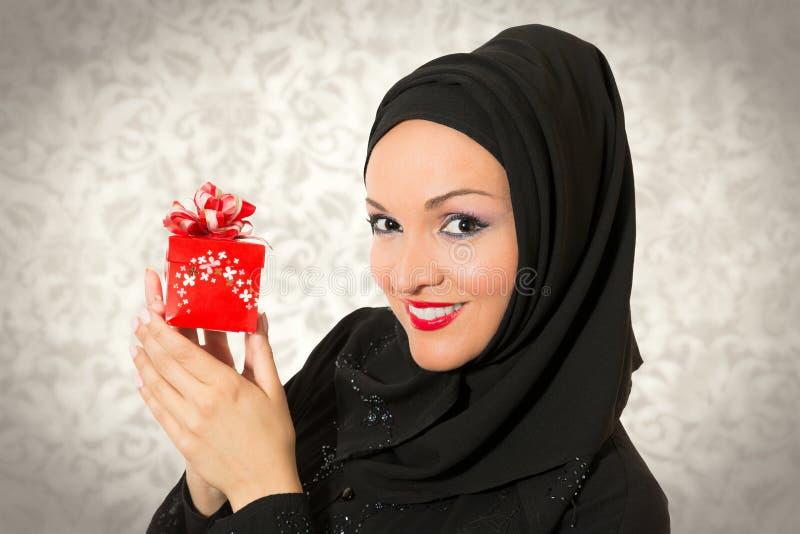 Αραβική γυναίκα, παραδοσιακό ντυμένο κράτημα παρών στοκ εικόνα