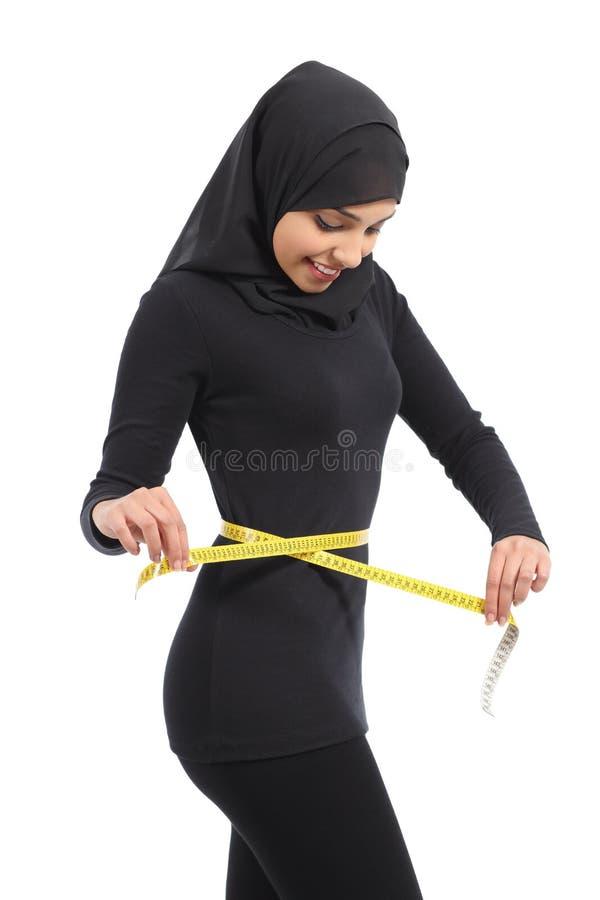 Αραβική γυναίκα που μετρά τη μέση με μια ταινία μέτρου στοκ εικόνες