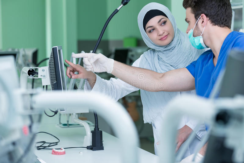 Αραβικοί σπουδαστές με το hijab εργαζόμενοι στην οδοντοστοιχία, ψεύτικα δόντια στοκ εικόνα με δικαίωμα ελεύθερης χρήσης