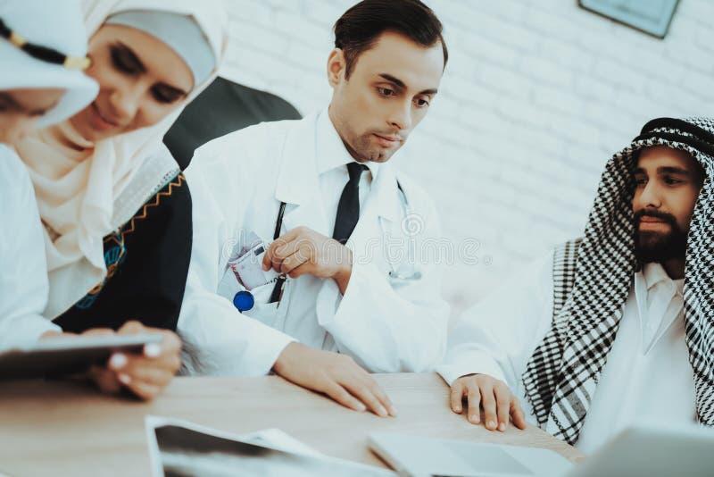 Αραβικός ασθενής που δίνει τα χρήματα ευρώ στο γιατρό στοκ εικόνες με δικαίωμα ελεύθερης χρήσης