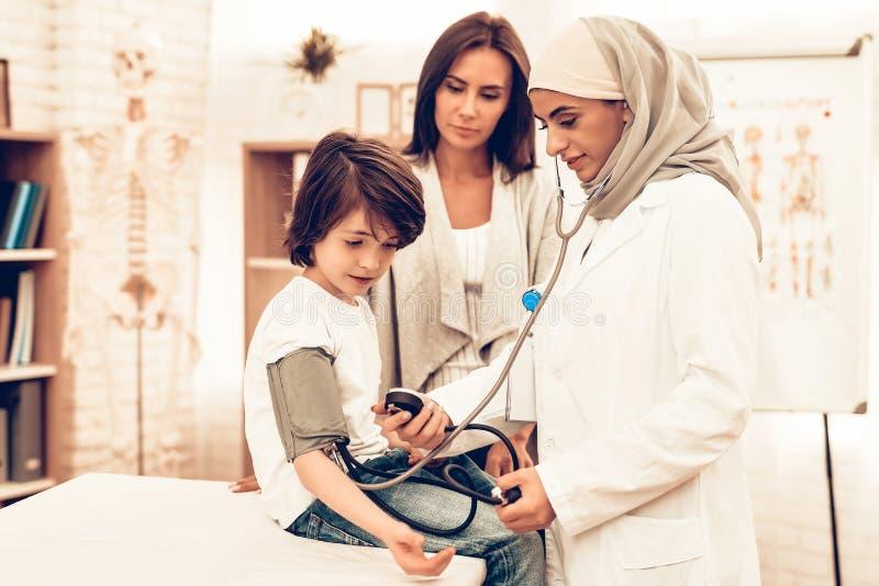 Αραβικός θηλυκός γιατρός που ελέγχει το αγόρι πίεσης του αίματος στοκ φωτογραφία με δικαίωμα ελεύθερης χρήσης