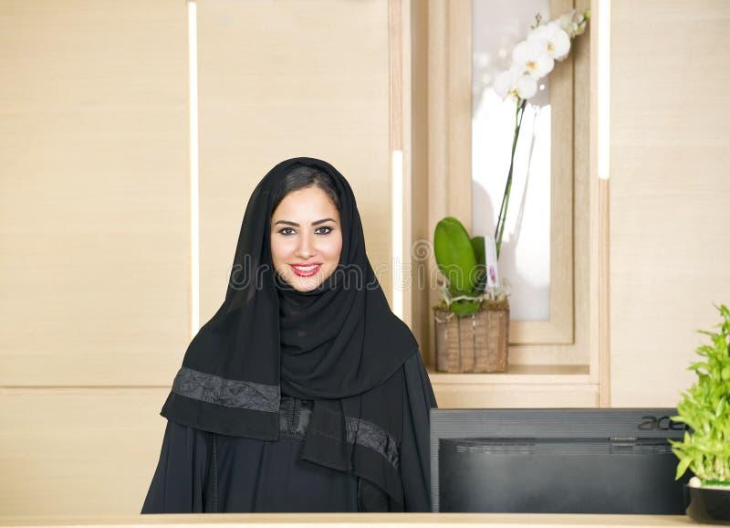 Αραβικός ρεσεψιονίστ που βοηθά έναν πελάτη στο μπροστινό γραφείο στοκ εικόνες