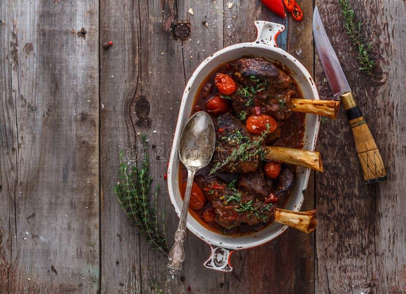 Αργές μαγειρευμένες κνήμες αρνιών με την ντομάτα και τα κοπάδια, διάστημα αντιγράφων στοκ εικόνα με δικαίωμα ελεύθερης χρήσης