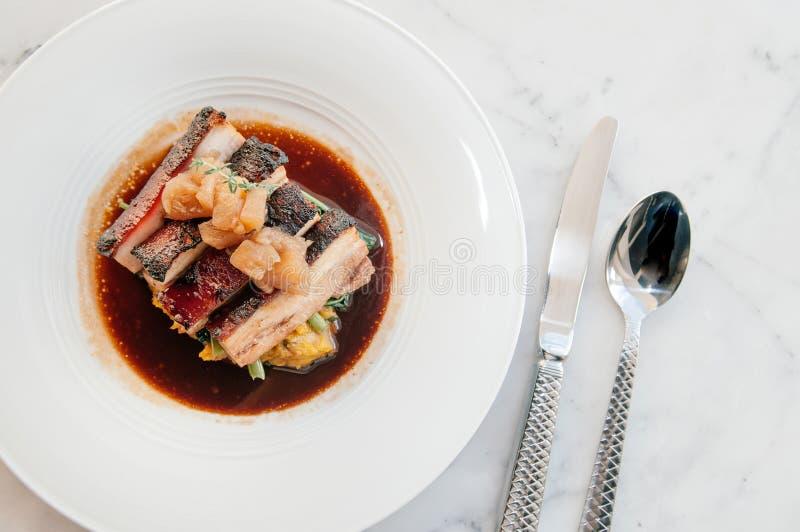 Αργή κοιλιά χοιρινού κρέατος στην καφετιά σάλτσα με τα λαχανικά, σύγχρονες ράχες στοκ εικόνες με δικαίωμα ελεύθερης χρήσης
