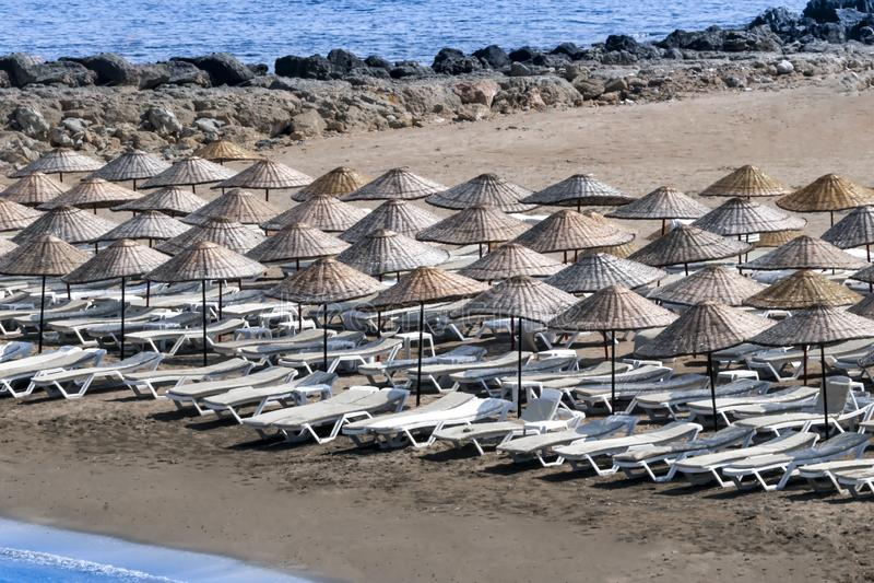 Αργόσχολοι και ομπρέλες ήλιων στην παραλία σε ένα ηλιόλουστο θερινό πρωί στοκ φωτογραφία