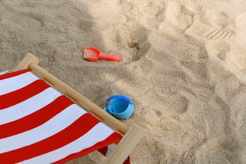 Αργόσχολος ήλιων & πλαστικός digger στη σκιά στην άμμο στοκ φωτογραφία
