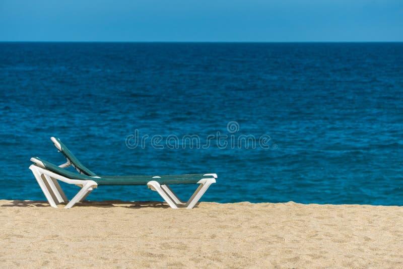 Αργόσχολος ήλιων στην αμμώδη παραλία με την τυρκουάζ θάλασσα και το μπλε ουρανό στοκ εικόνες με δικαίωμα ελεύθερης χρήσης