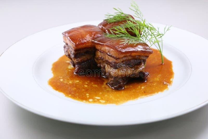 Αργό κρέας χοιρινού κρέατος στο κινεζικό ύφος με τα χορτάρια στο άσπρο πιάτο στοκ φωτογραφία