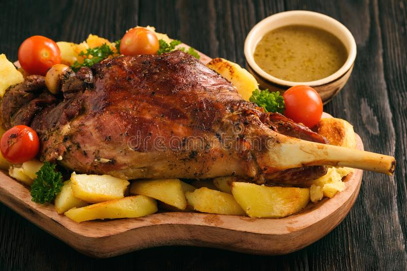 Αργό ψημένο πόδι αρνιών με τις πατάτες και τη σάλτσα στοκ εικόνες