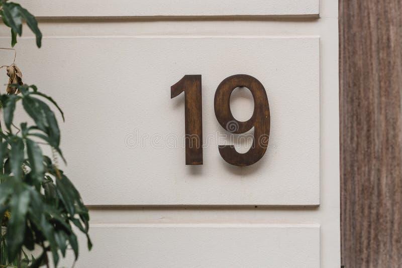 Αριθμητικά στοιχεία με επίστρωση χάλυβα που δείχνουν τον αριθμό οικίας δεκαεννέα Αριθμός σπιτιού σε τοίχο σπιτιού στοκ φωτογραφίες