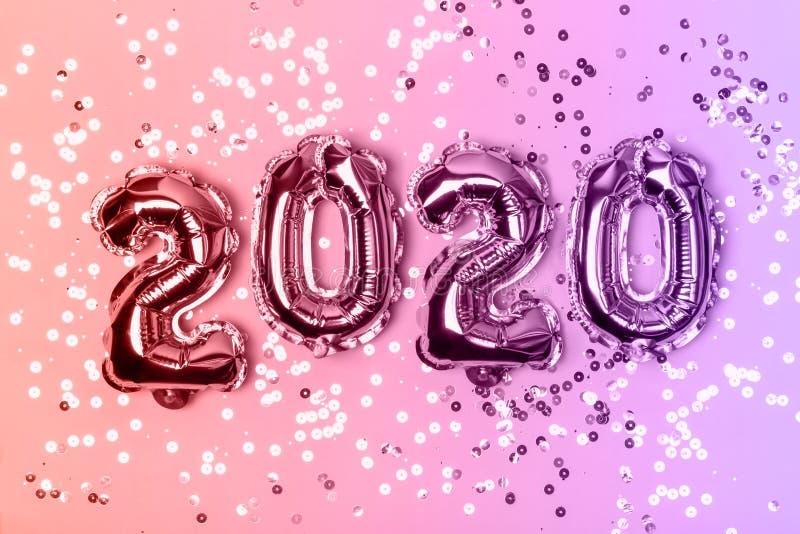 Αριθμοί 2020 που γίνεται από τα μπαλόνια φύλλων αλουμινίου στο υπόβαθρο και τα σπινθηρίσματα φω'των νέου Έννοια Χριστουγέννων στοκ φωτογραφία