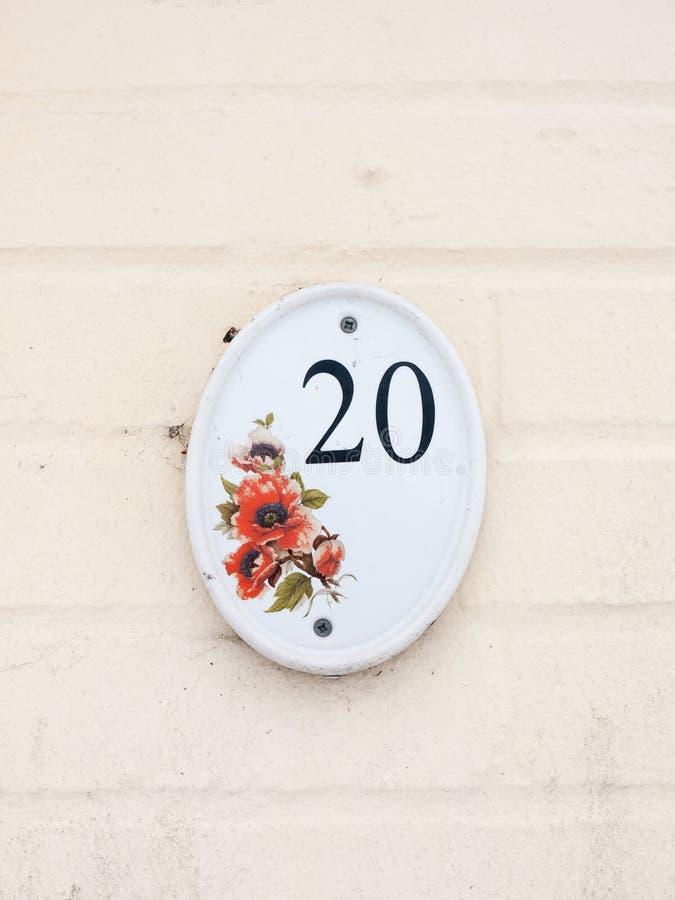 αριθμός πινακίδας αυτοκινήτου σπιτιών στον άσπρο τοίχο αριθμός 20 εξωτερικού σχέδιο λουλουδιών στοκ εικόνα