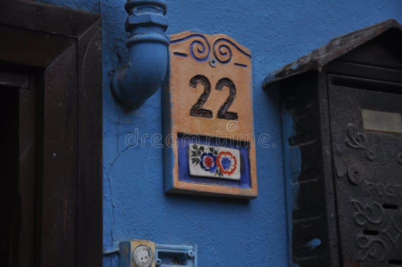 Αριθμός πορτών με τα λουλούδια Μπλε χρώμα τοίχων r Παλαιό χαριτωμένο νοσταλγικό σπίτι στοκ εικόνες με δικαίωμα ελεύθερης χρήσης