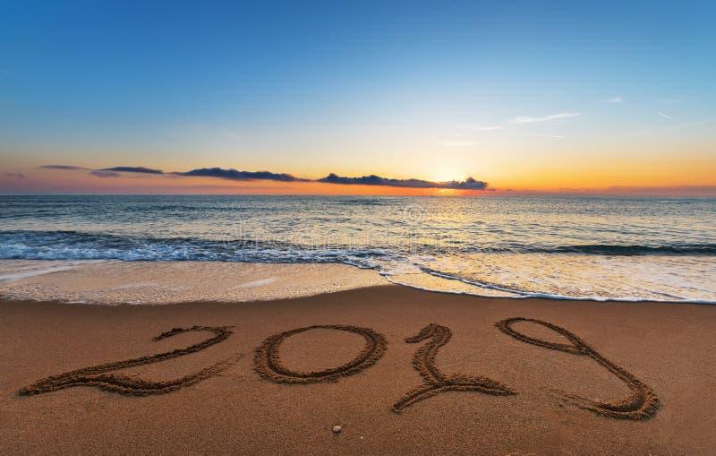 Αριθμός 2019 που γράφεται στην άμμο ακτών στην ανατολή στοκ εικόνα