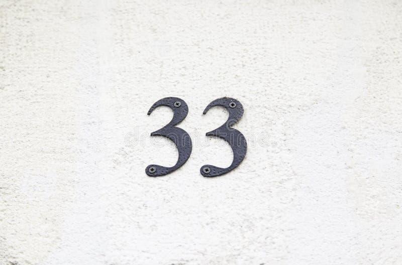Αριθμός τριάντα τρία στον τοίχο ενός σπιτιού στοκ φωτογραφία
