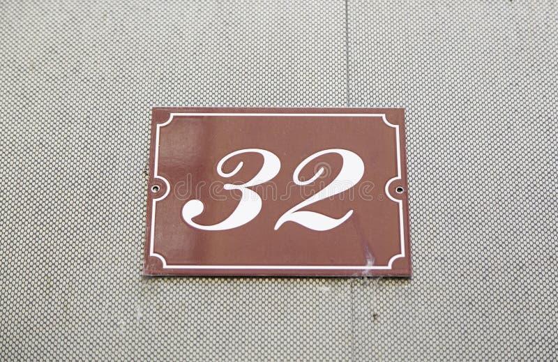 Αριθμός τριάντα δύο στον τοίχο ενός σπιτιού στοκ φωτογραφίες