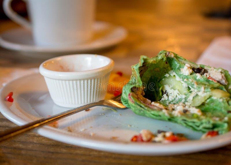 Αριστερό πέρα από το πράσινο περικάλυμμα σπανακιού στο πιάτο στοκ εικόνες